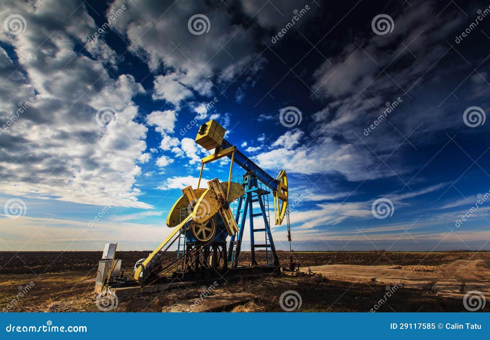 Puits de pétrole fonctionnant profilé sur le ciel nuageux excessif