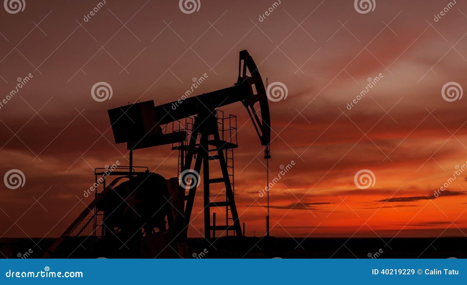 Puits fonctionnant de pétrole et de gaz profilé sur le ciel de coucher du soleil