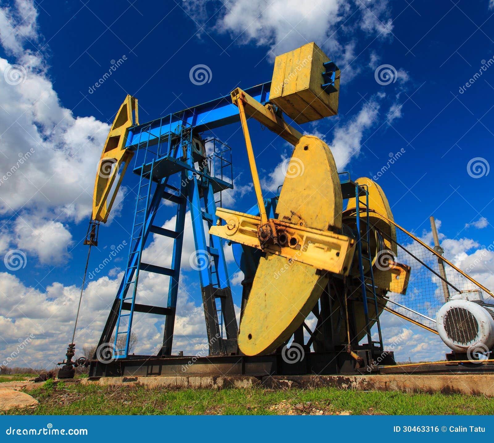 Puits fonctionnant de pétrole et de gaz profilé sur le ciel ensoleillé
