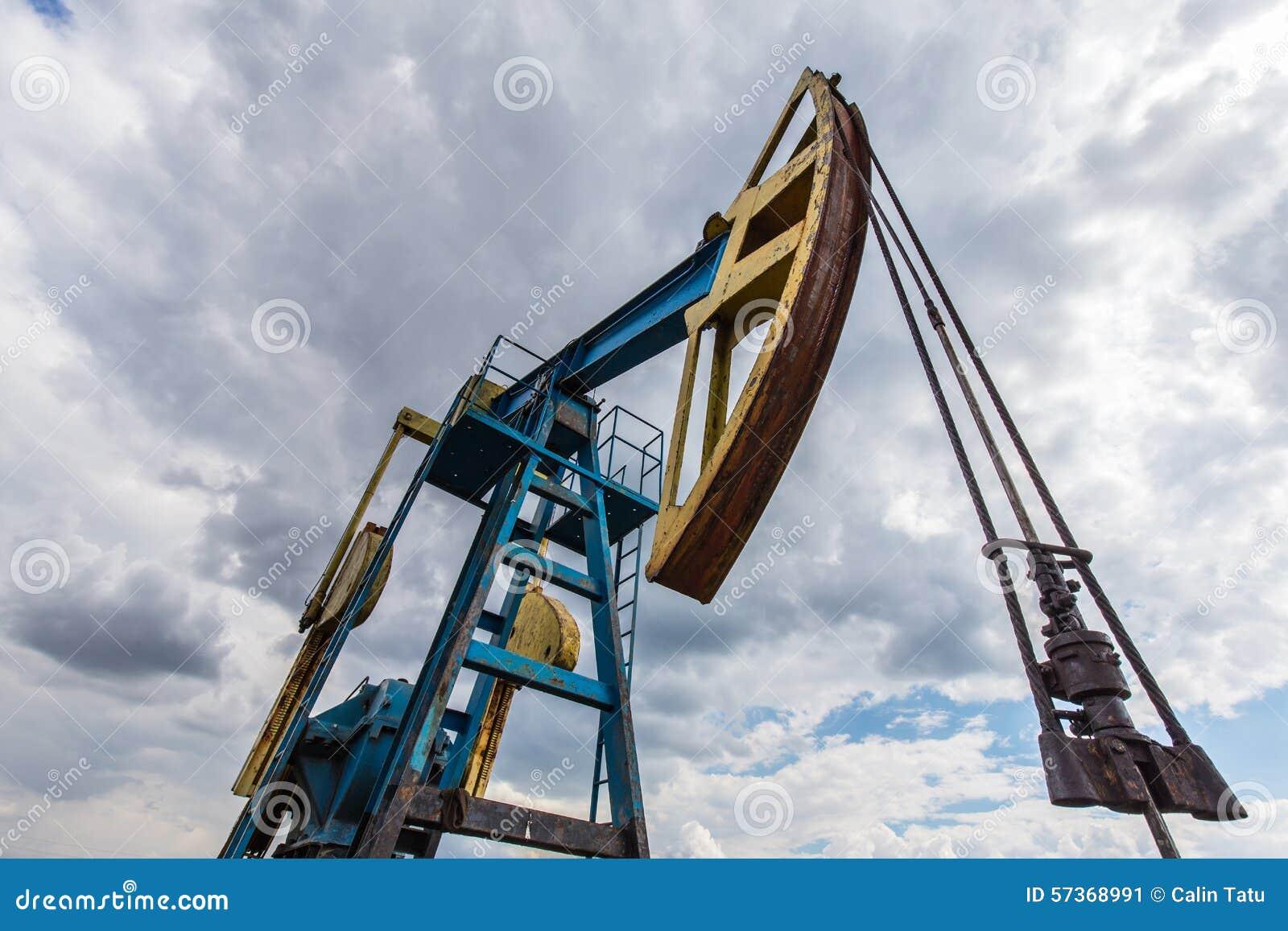 Puits fonctionnant de pétrole et de gaz profilé sur le ciel nuageux