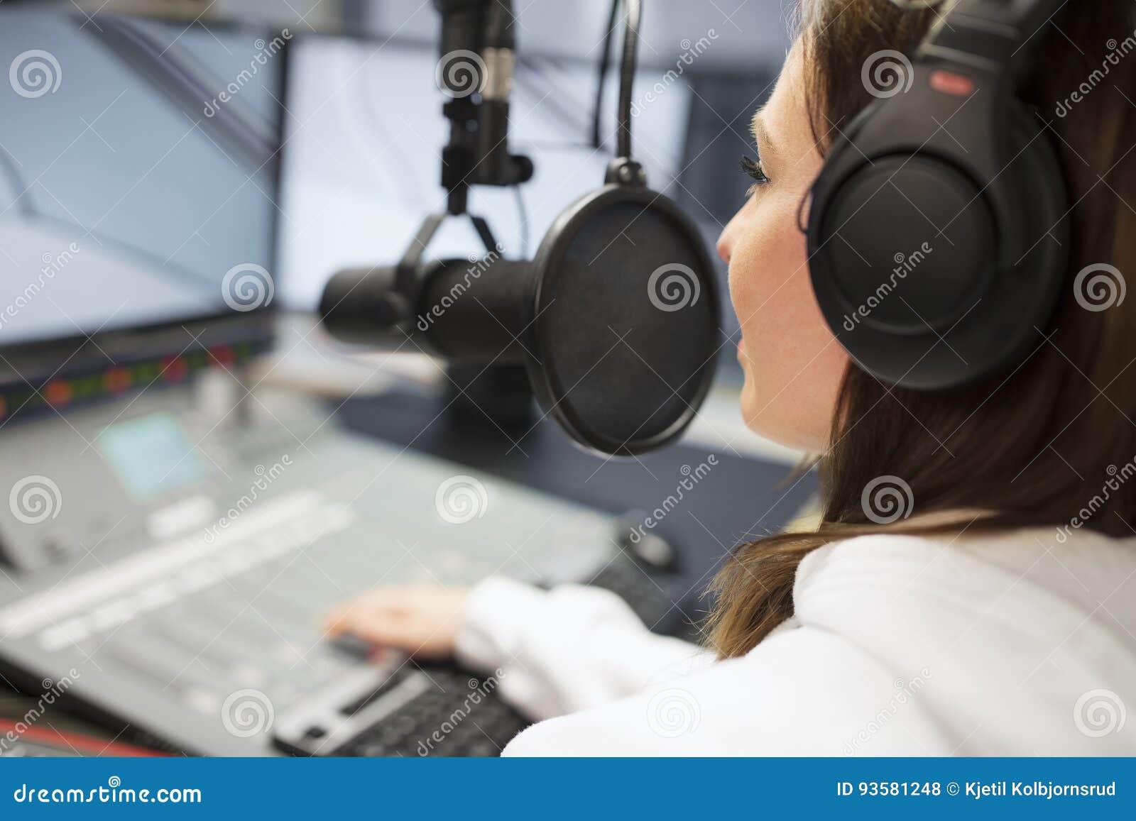 Puleggia tenditrice Wearing Headphones While che utilizza microfono nello studio radiofonico