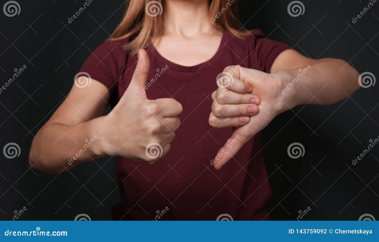 PULGAR de la demostración de la mujer arriba y abajo del gesto en lenguaje de signos en fondo negro