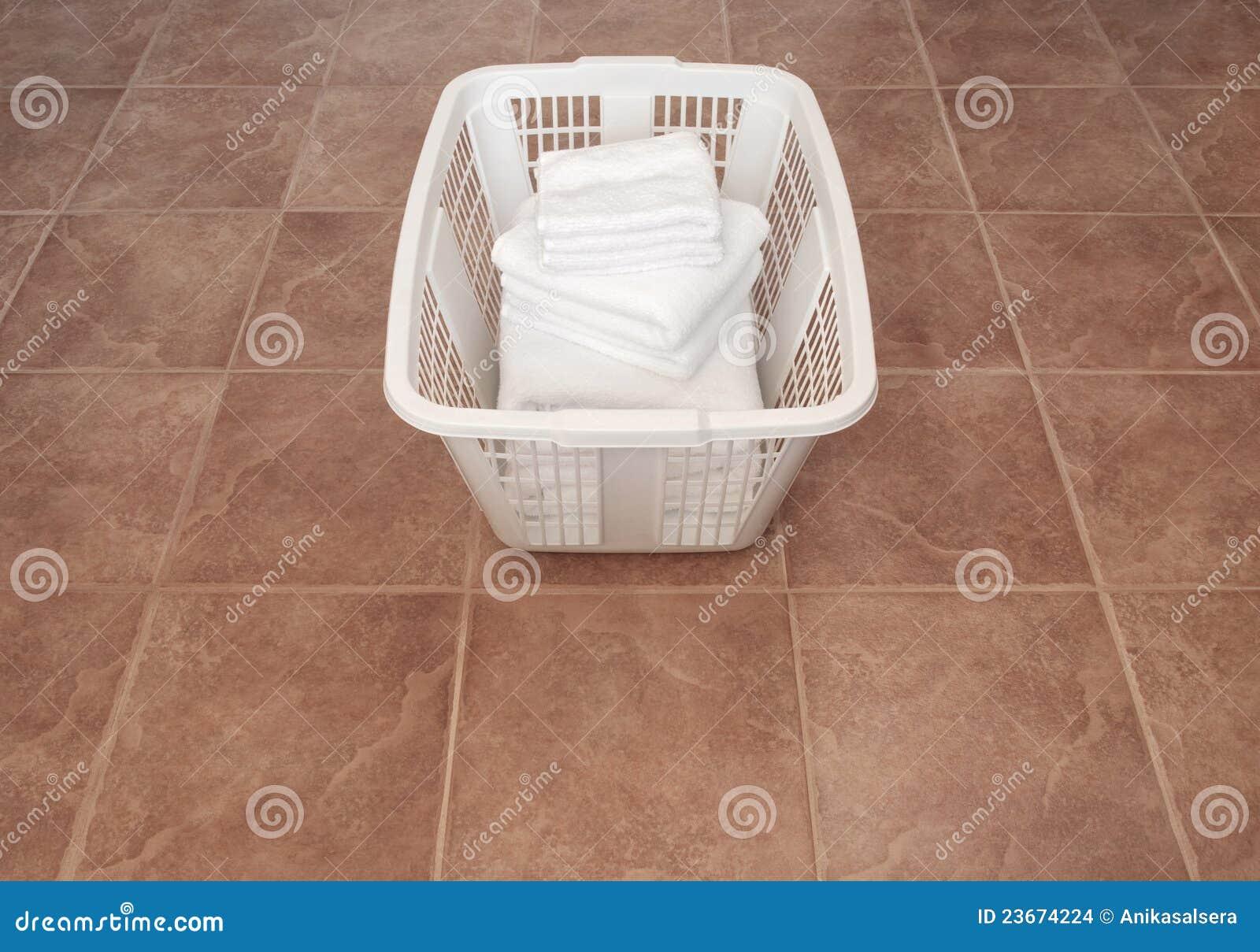 18ad2ed4bb Pulisca i tovaglioli bianchi in un cestino di lavanderia sul pavimento di  ceramica.
