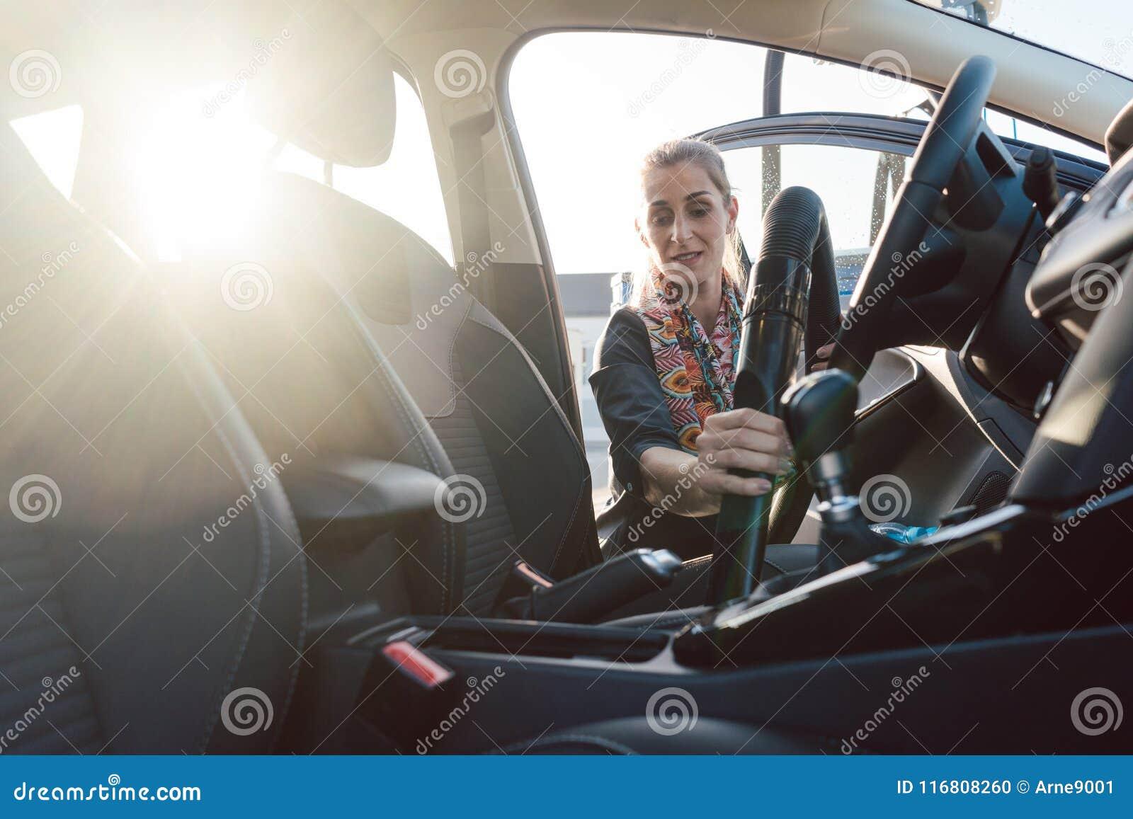 Pulizia della donna dentro dell automobile