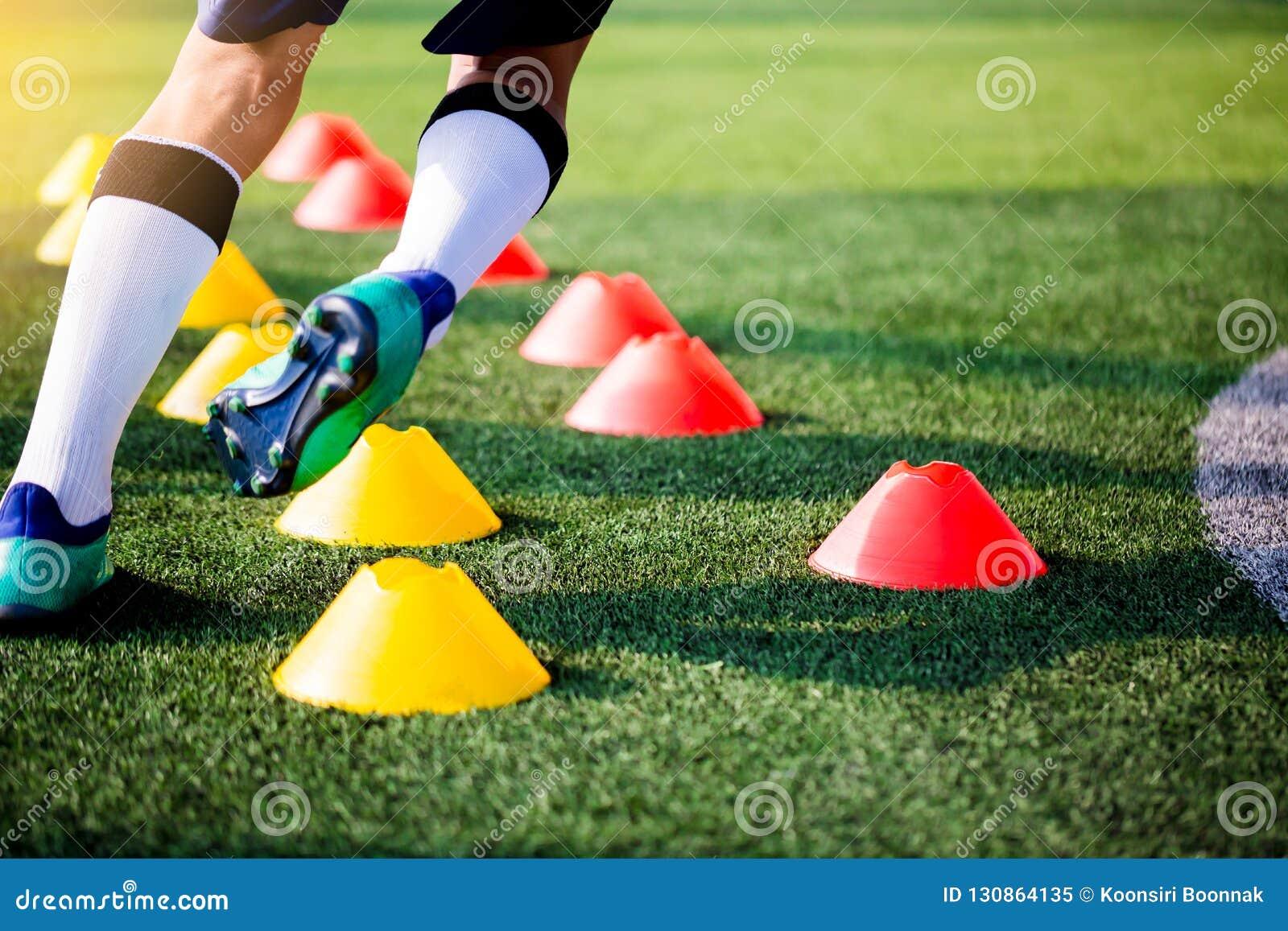 Pulser et saut de footballeur entre les marqueurs de cône sur l art vert