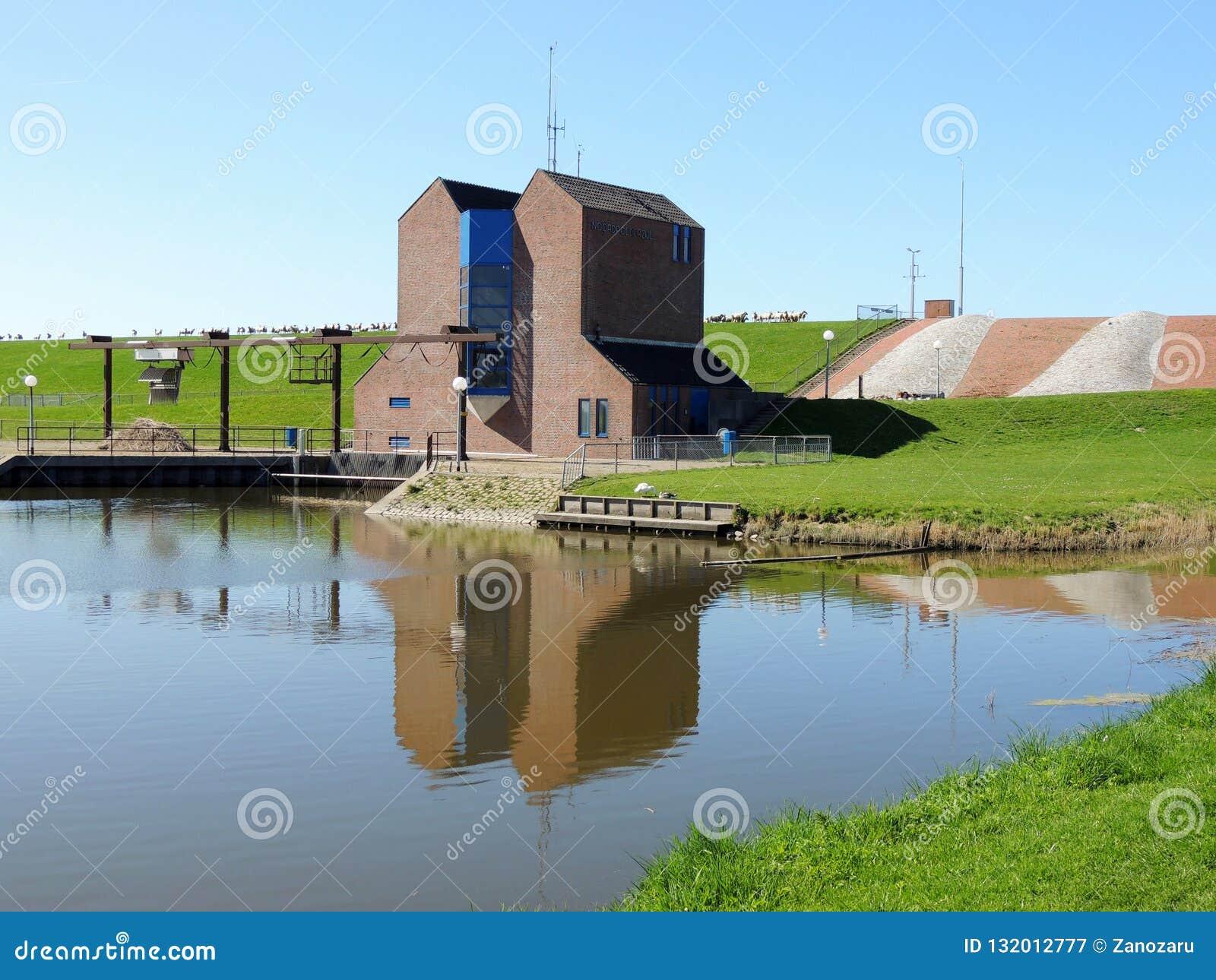 Pumpa station Nordpolderzijl Noordpolderzijl i landskapet av Groningen, Nederländerna Fördämning på Nordsjö