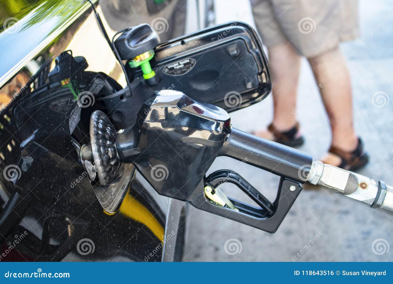 Pumpendes Gas - Nahaufnahme der Gaspumpendüse eingefügt zu in den Autogasbehälter mit den Beinen des Kunden kurz gesagt im Hinter