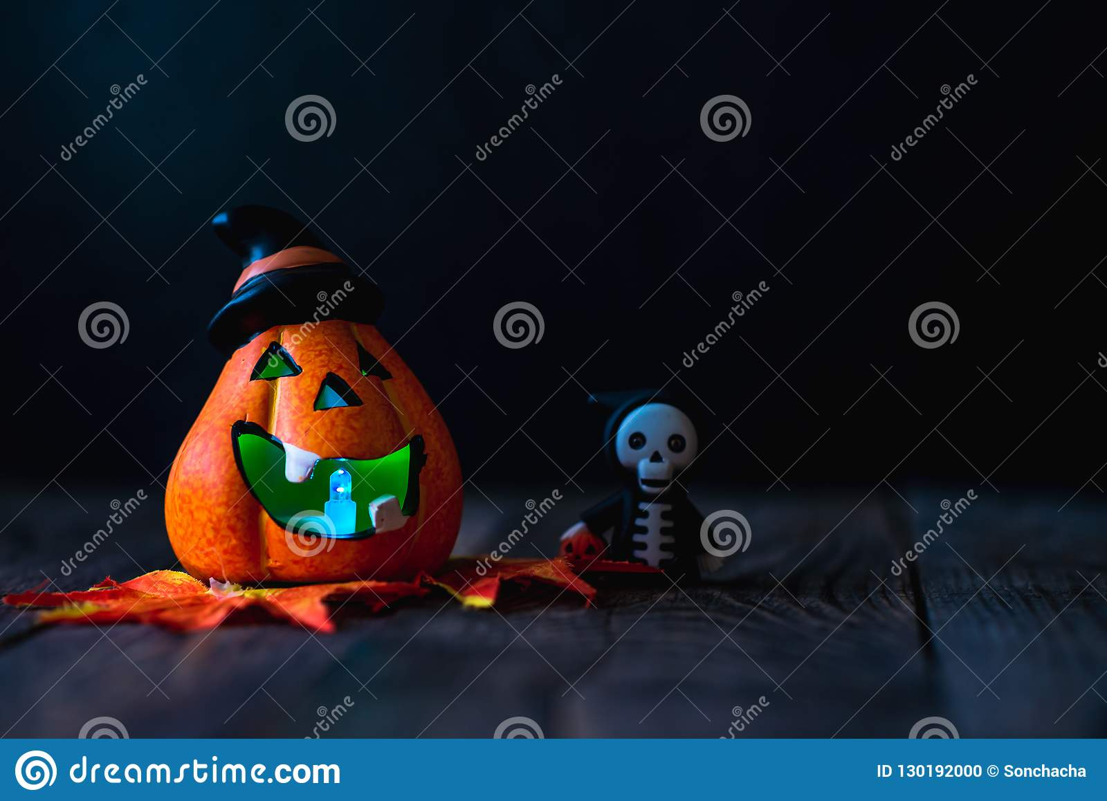 Pumpkin with a face and a skeleton in a hoodie