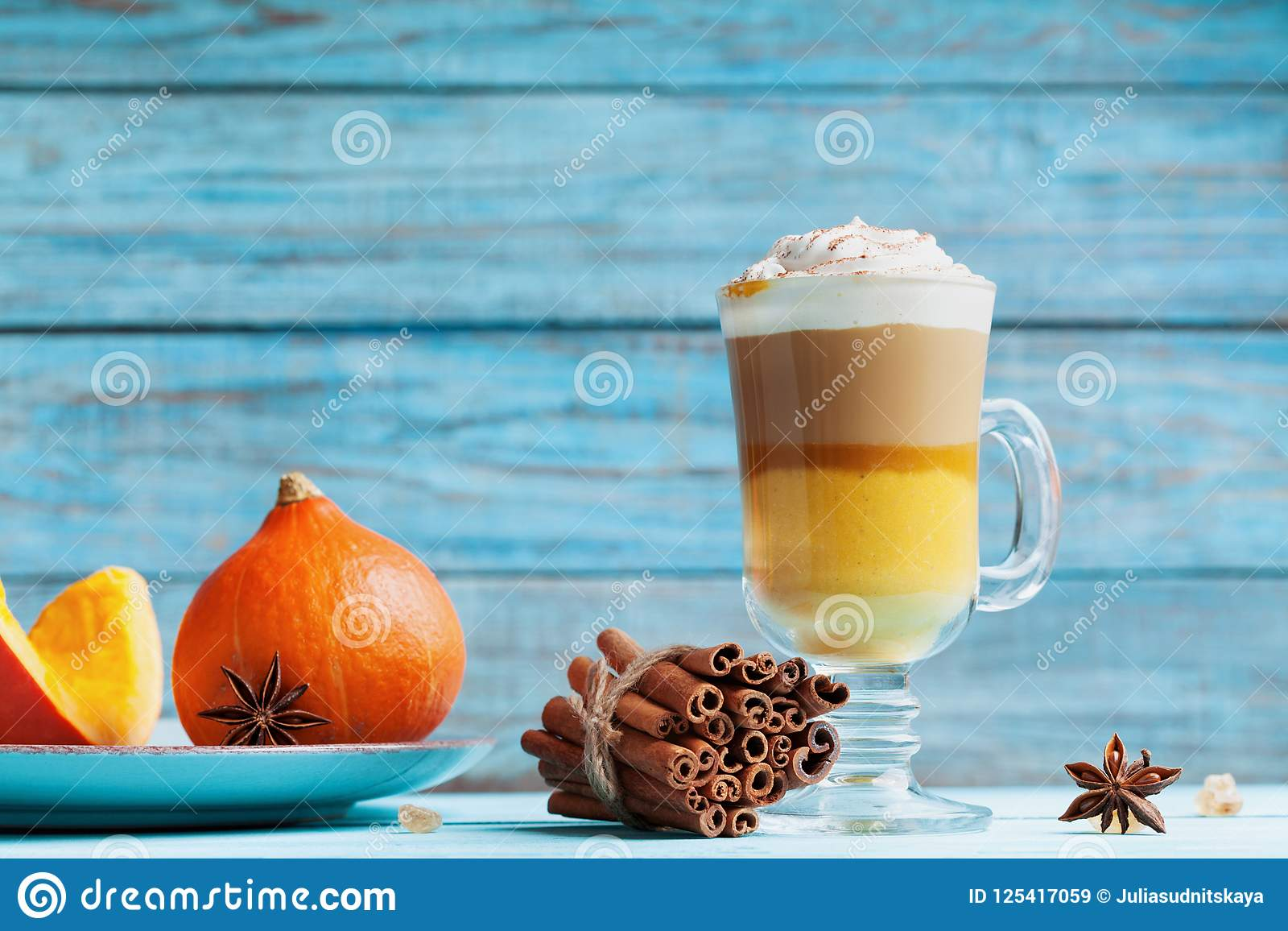 Pumpkin spiced latte or coffee in glass on turquoise rustic table. Autumn, fall or winter hot drink.