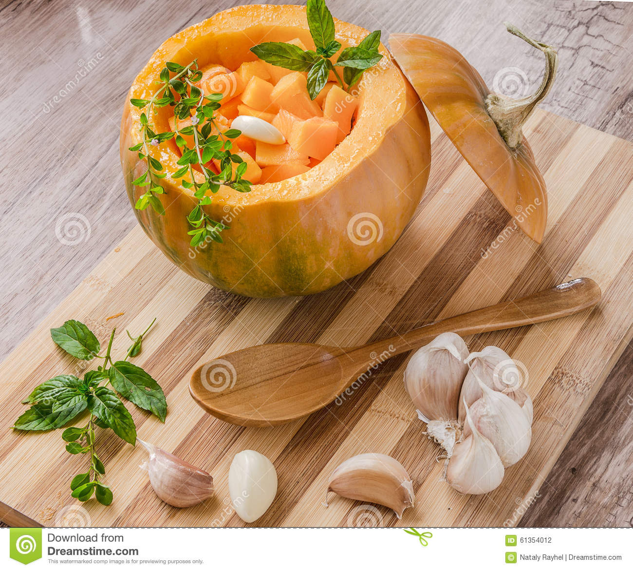 Pumpkin stuffed with garlic and herbs on a cutting board.