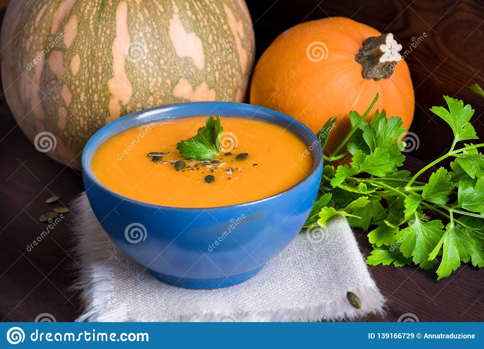 Pumpkin vegetarian soup in a blue bowl served with parsley, olive oil and pumpkin seeds on a dark wooden background