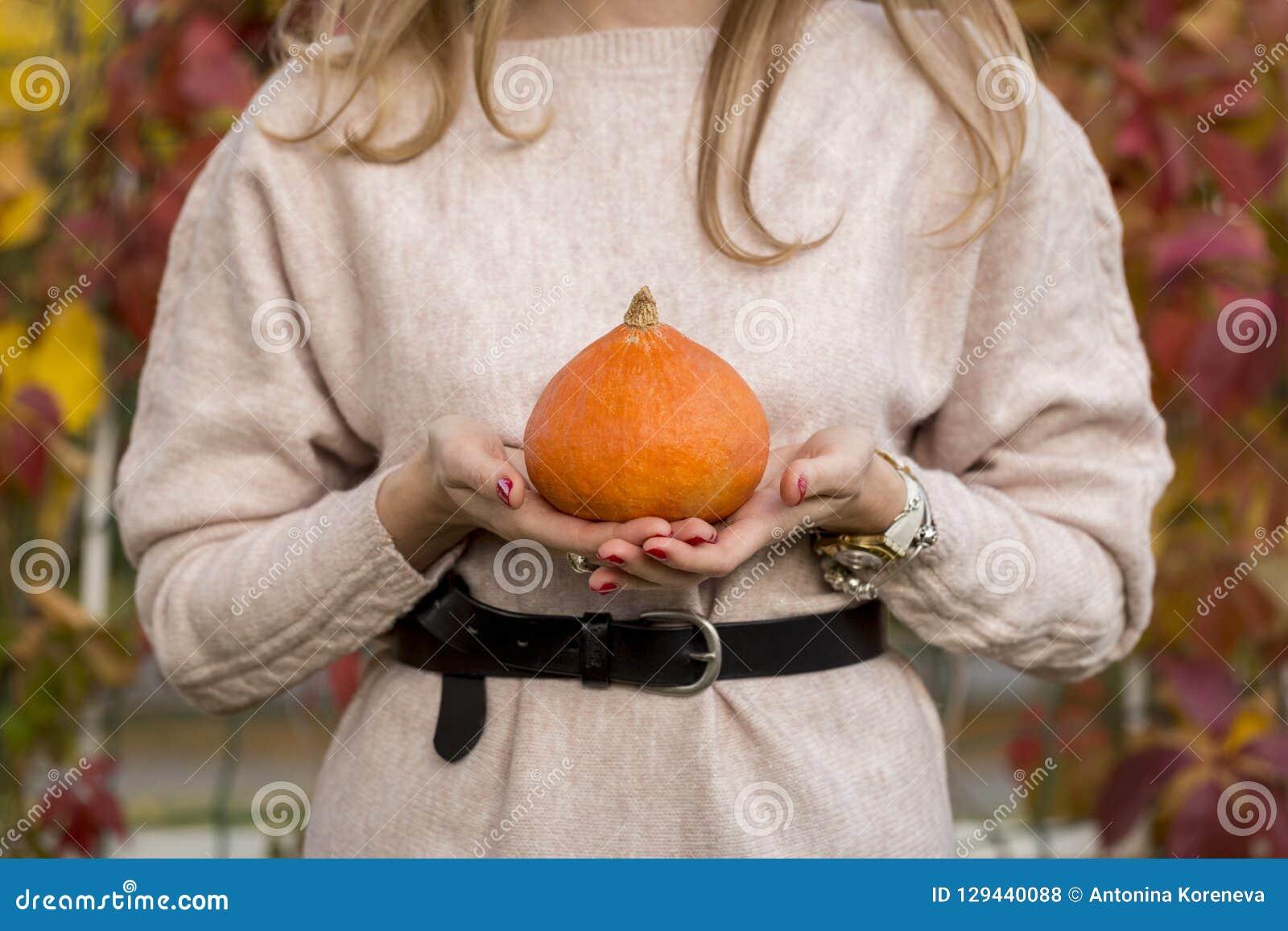 Pumpkin in woman hand out door