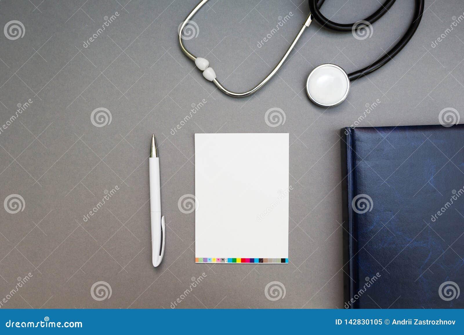 Punkter, en stetoskop och en anteckningsbok på en grå bakgrund, arbetsplatsen av doktorn
