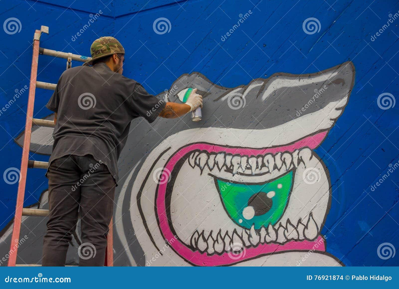 PUNTA DEL ESTE, URUGUAY - 6. MAI 2016: junger Mann, der in einem Treppenhaus beendet Graffiti steht