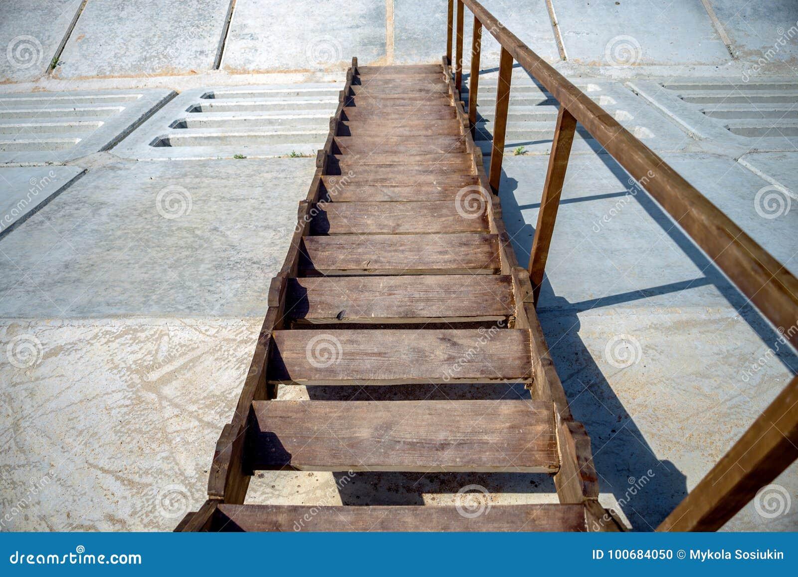 Punti di legno che scendono un pendio, scala di legno con una che recinta