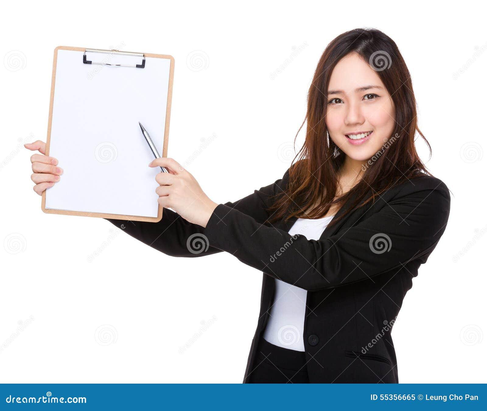 Punto di penna asiatico della donna di affari alla lavagna per appunti con carta in bianco