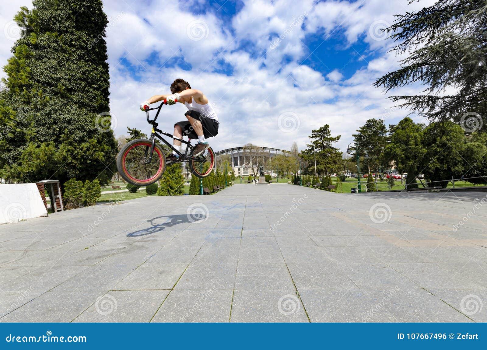 Punto di vista basso del ciclista abile che salta su su contro il cielo