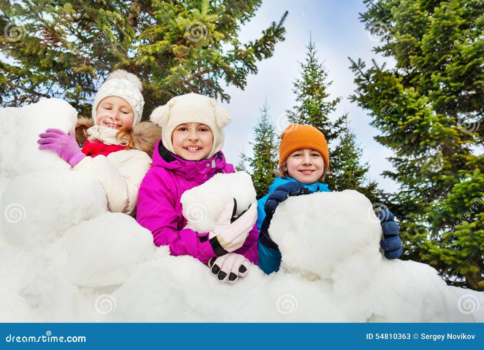 Punto di vista del primo piano dei bambini felici dietro la fortificazione della neve