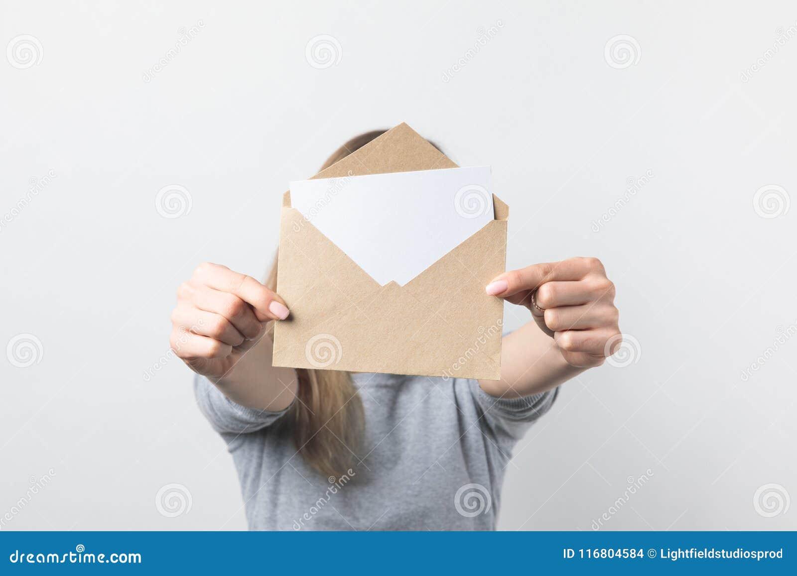 Punto di vista parziale della donna che mostra la busta di Kraft con la carta in bianco in mani