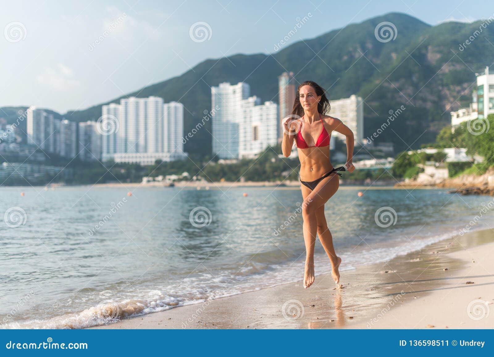 Punto di vista posteriore della ragazza esile di misura che corre a piedi nudi sul bikini d uso della spiaggia Giovane donna che