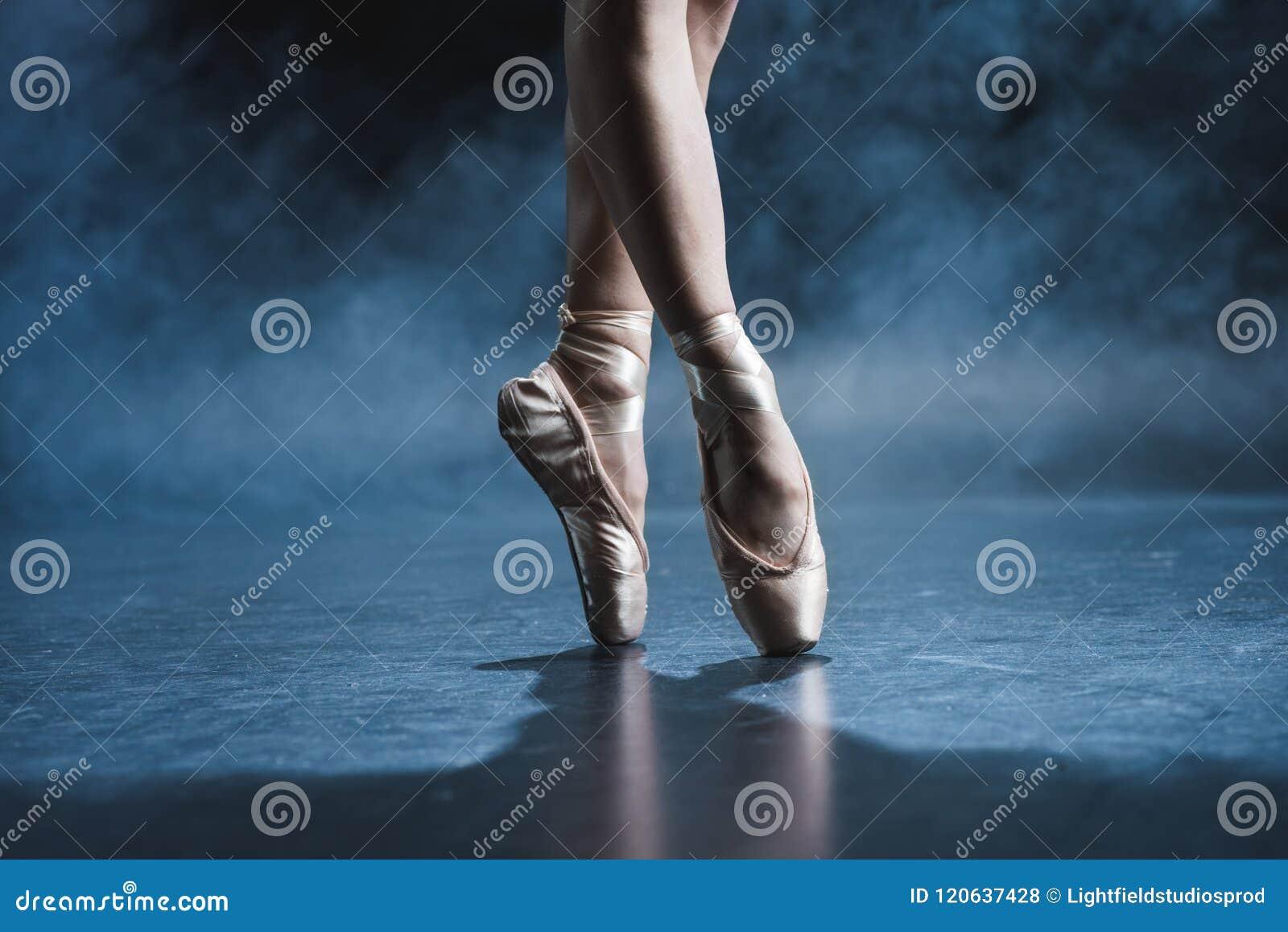 Punto di vista potato del ballerino di balletto in scarpe del pointe in studio scuro