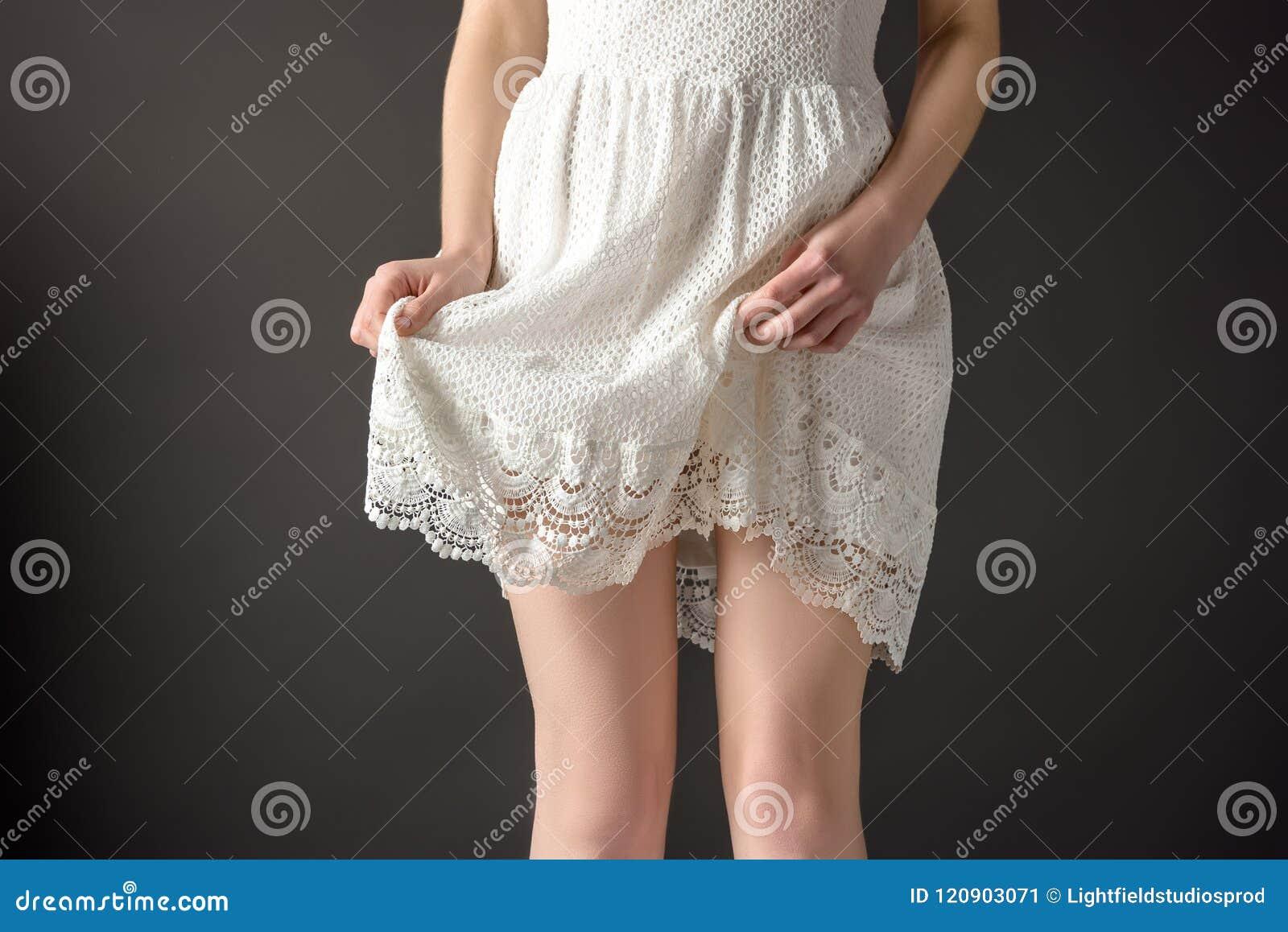 Punto di vista potato della ragazza che posa in vestito bianco elegante dal pizzo,