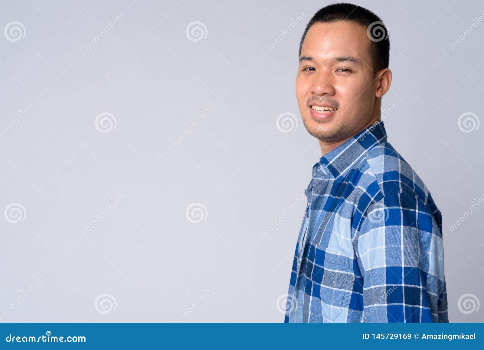 Punto di vista di profilo di giovane uomo asiatico felice dei pantaloni a vita bassa che esamina macchina fotografica