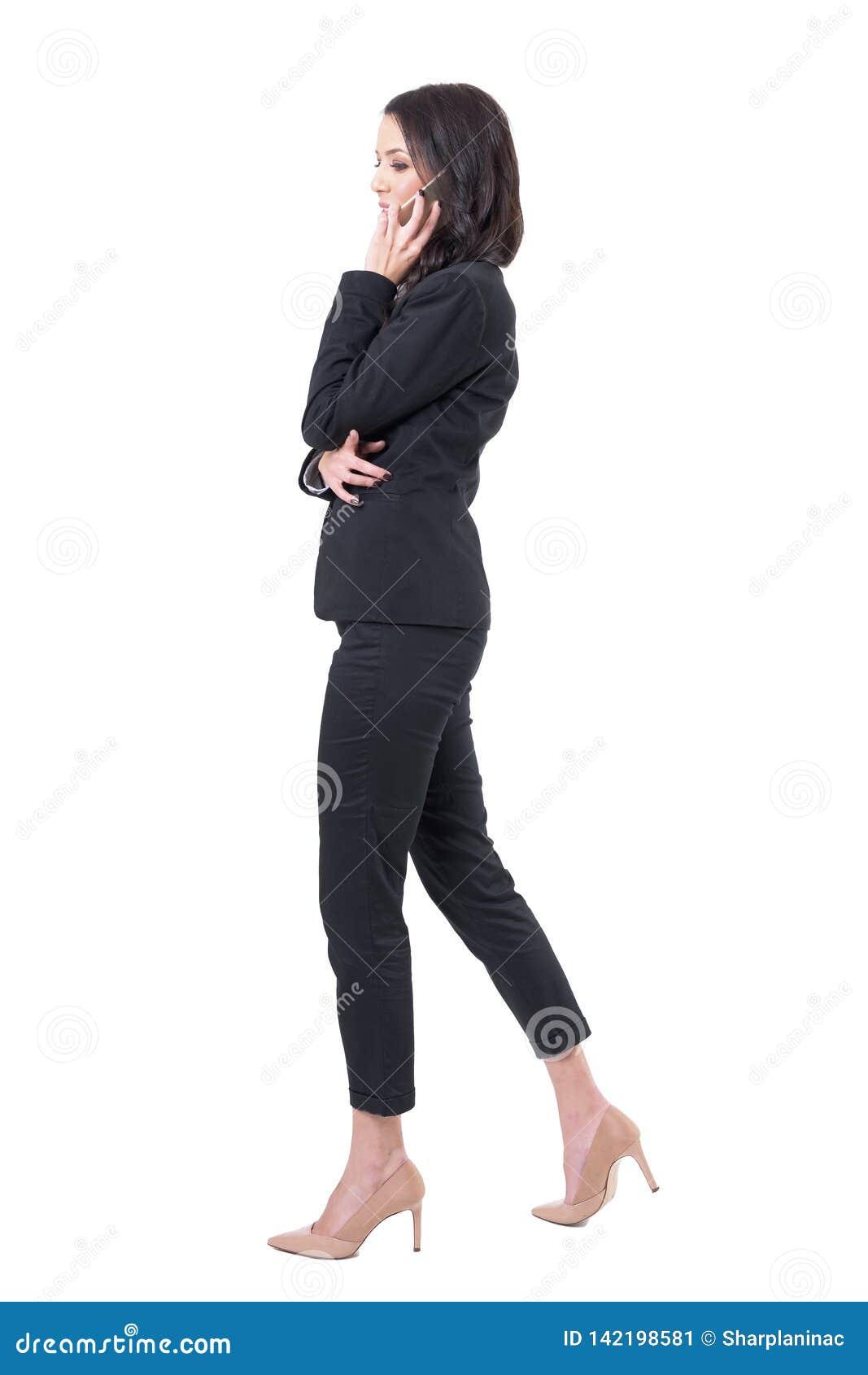 Punto di vista di profilo di riuscita giovane donna di affari che cammina e che fa le chiamate di telefono cellulare
