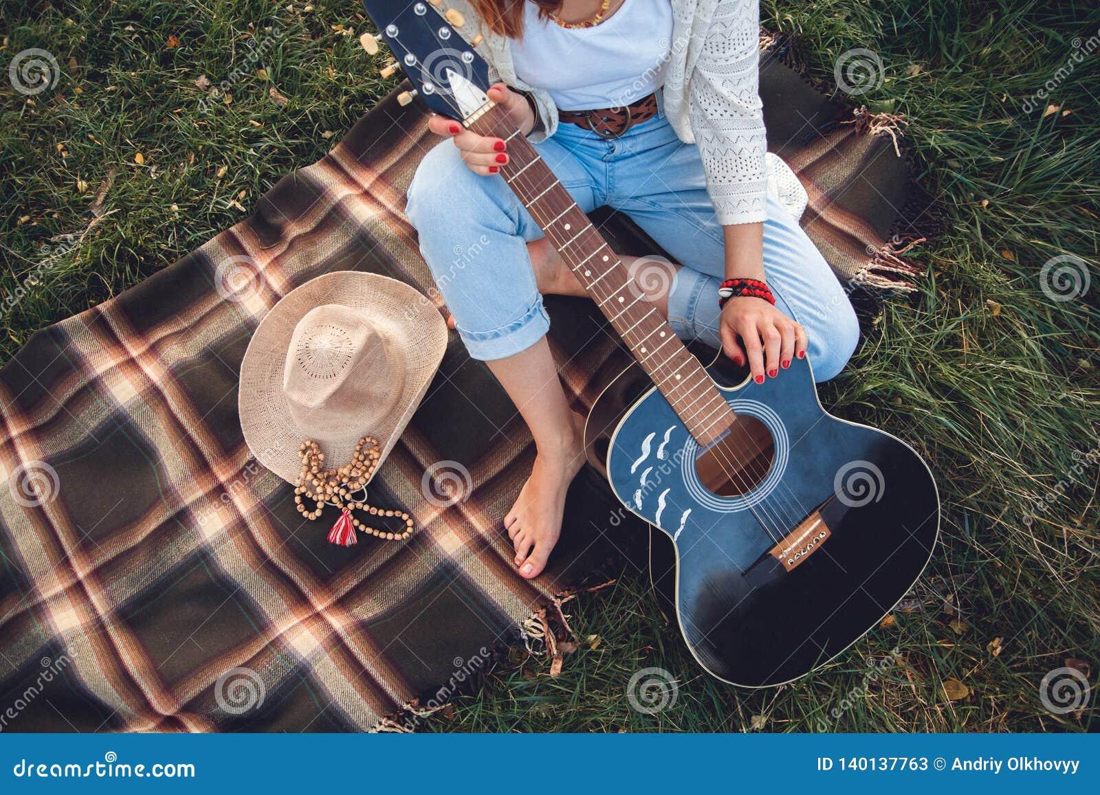 Punto di vista sopraelevato di bella donna con la chitarra che riposa sul prato inglese verde Vista superiore
