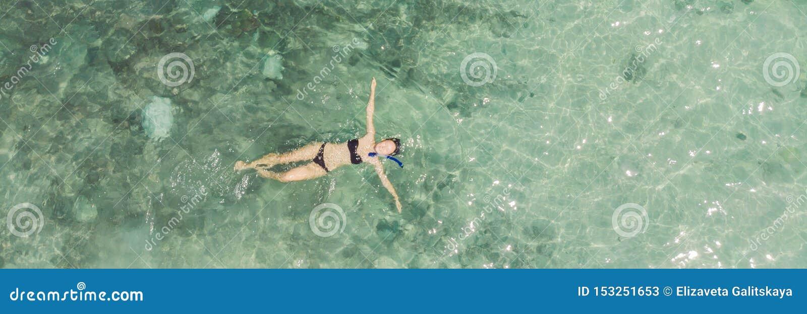 Punto di vista superiore aereo della donna che si immerge da sopra, nuoto dello snorkeler della ragazza in un acqua di mare tropi
