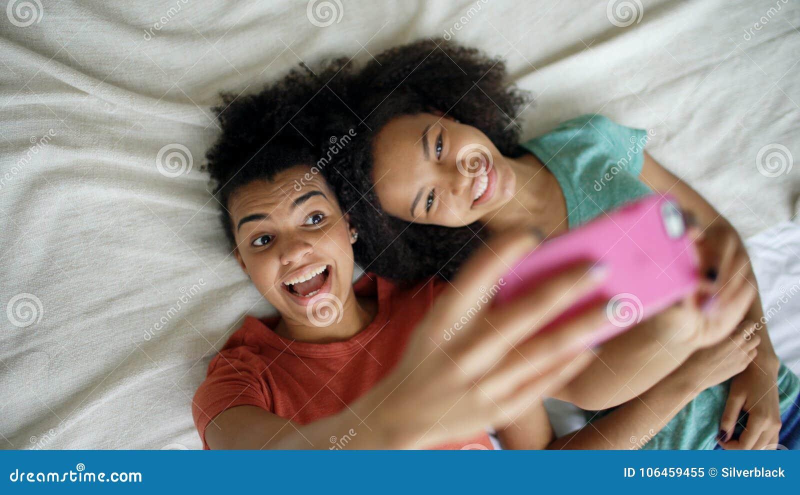 Tre amiche felici a casa in una camera da letto u foto stock