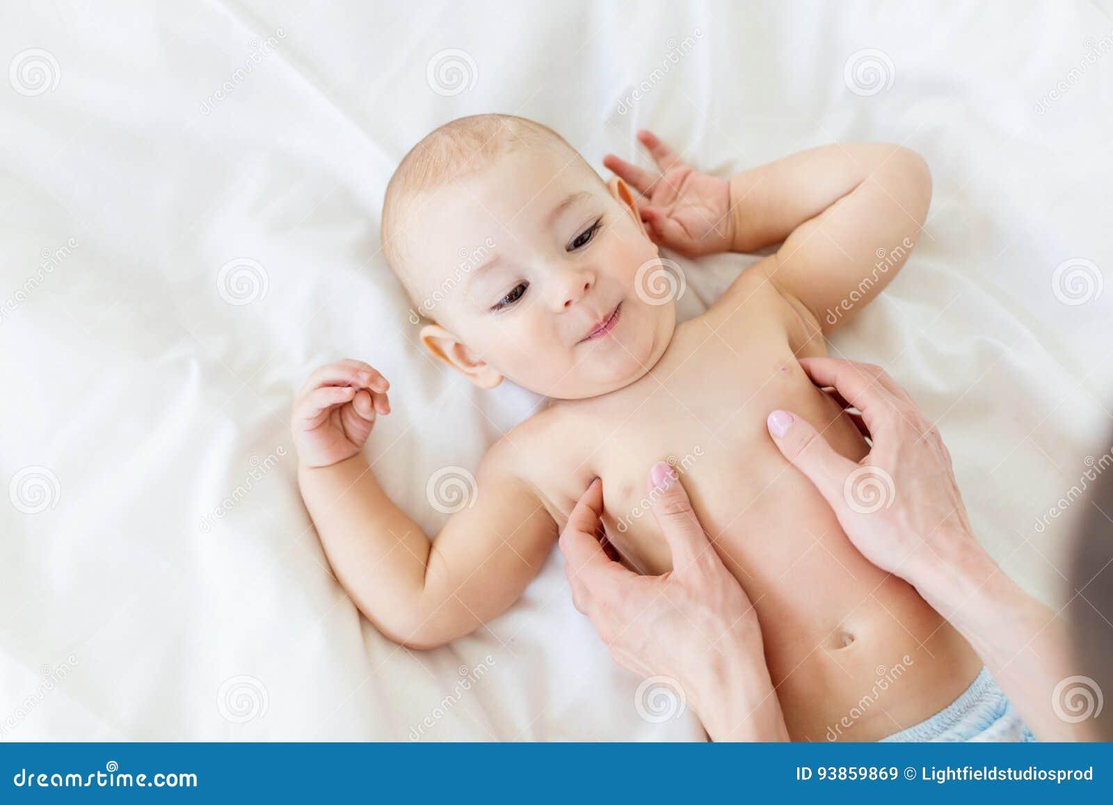 Punto di vista superiore della madre che massaggia neonato adorabile che si trova sul letto