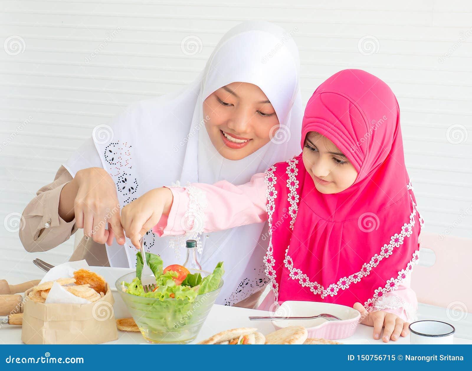 Punto musulmán de la madre a la ensalada vegetal mientras que la niña con el hijab rosado se divierte con la ensalada de mezcla p