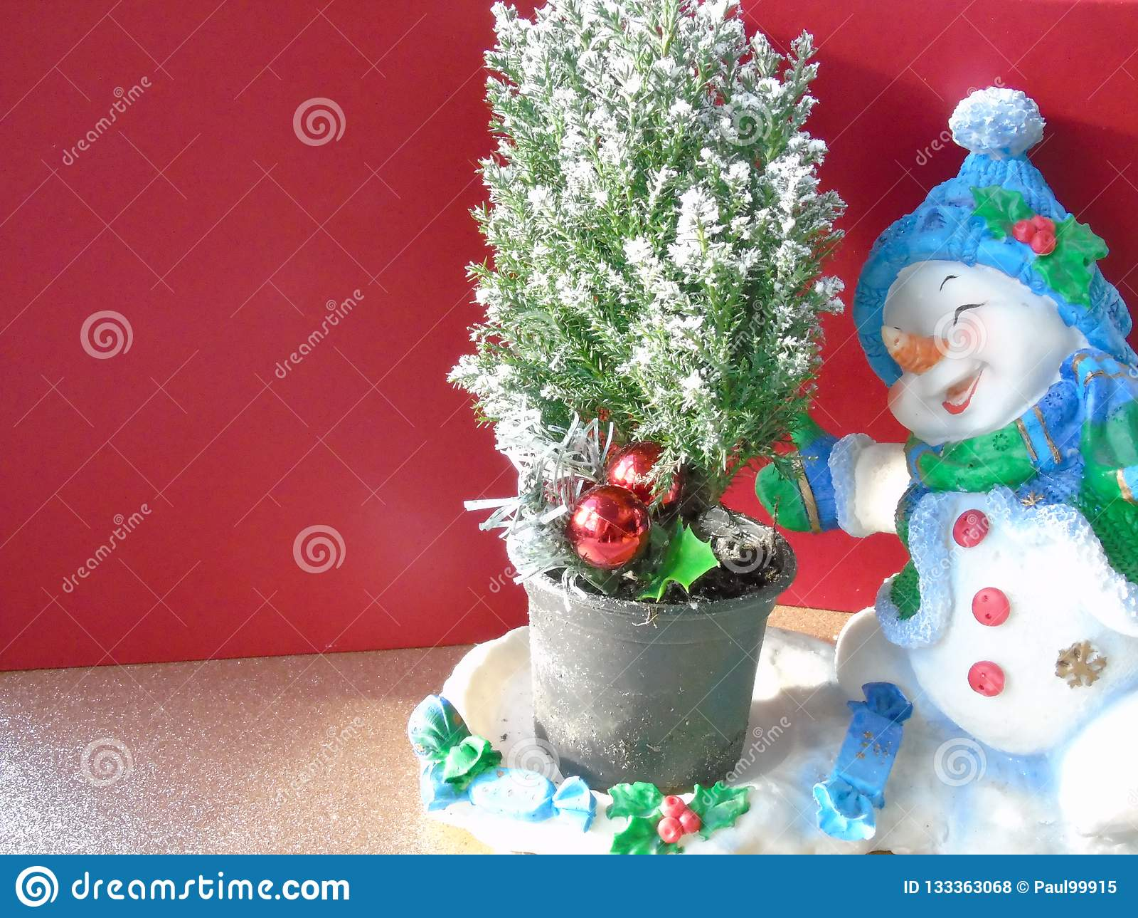 Pupazzo di neve allegro felice di Natale che pattina intorno ad un albero di natale