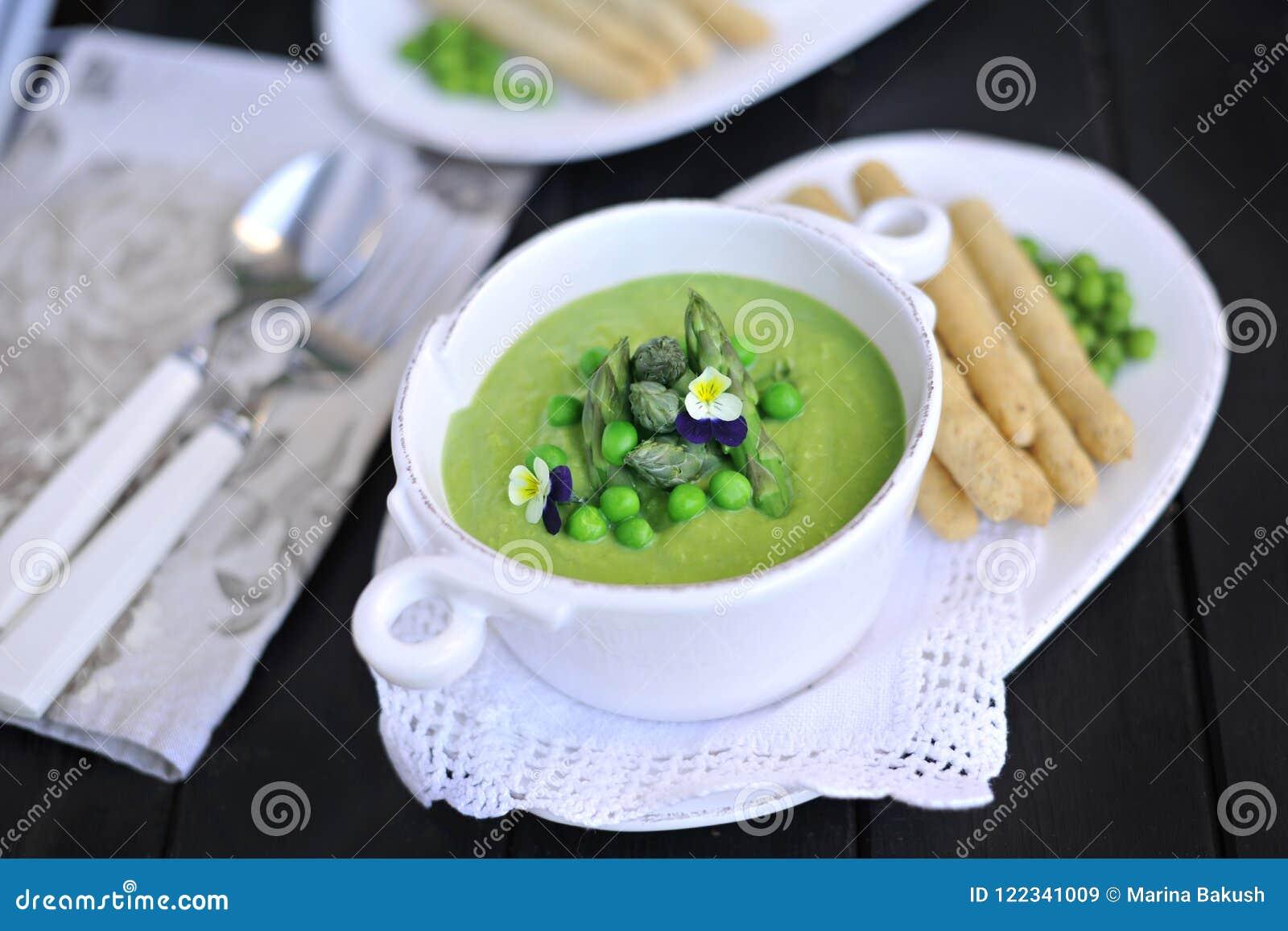 Purée de soupe avec les pois et l asperge décoré des violettes de fleurs fraîches Sur un fond noir dans les plats blancs Pain et