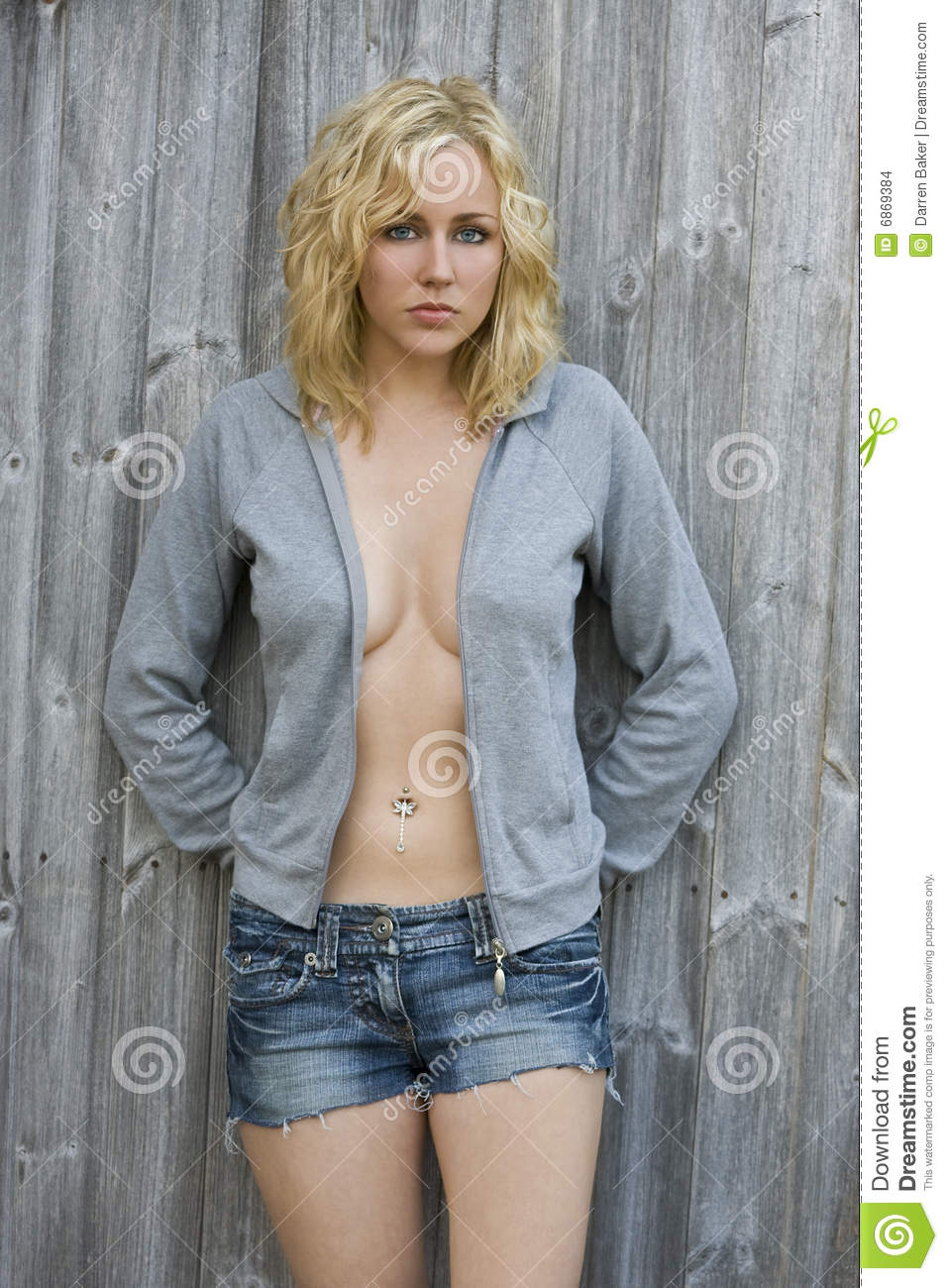 A beautiful blond haired blue eyed young woman looking in denim shorts and  a hooded top