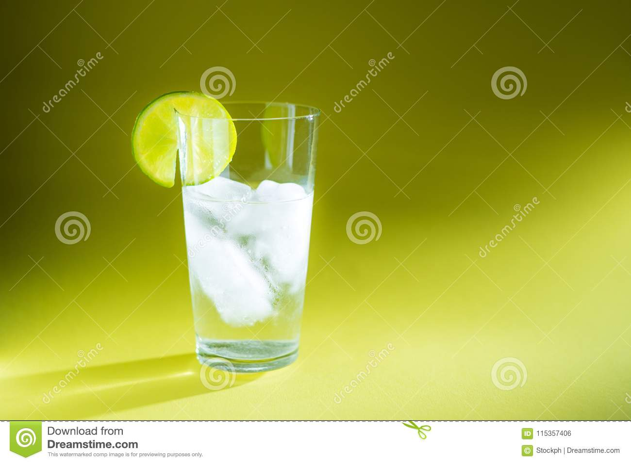 Pure water in a glass of real ice and a slice of fresh lime in the rays of light