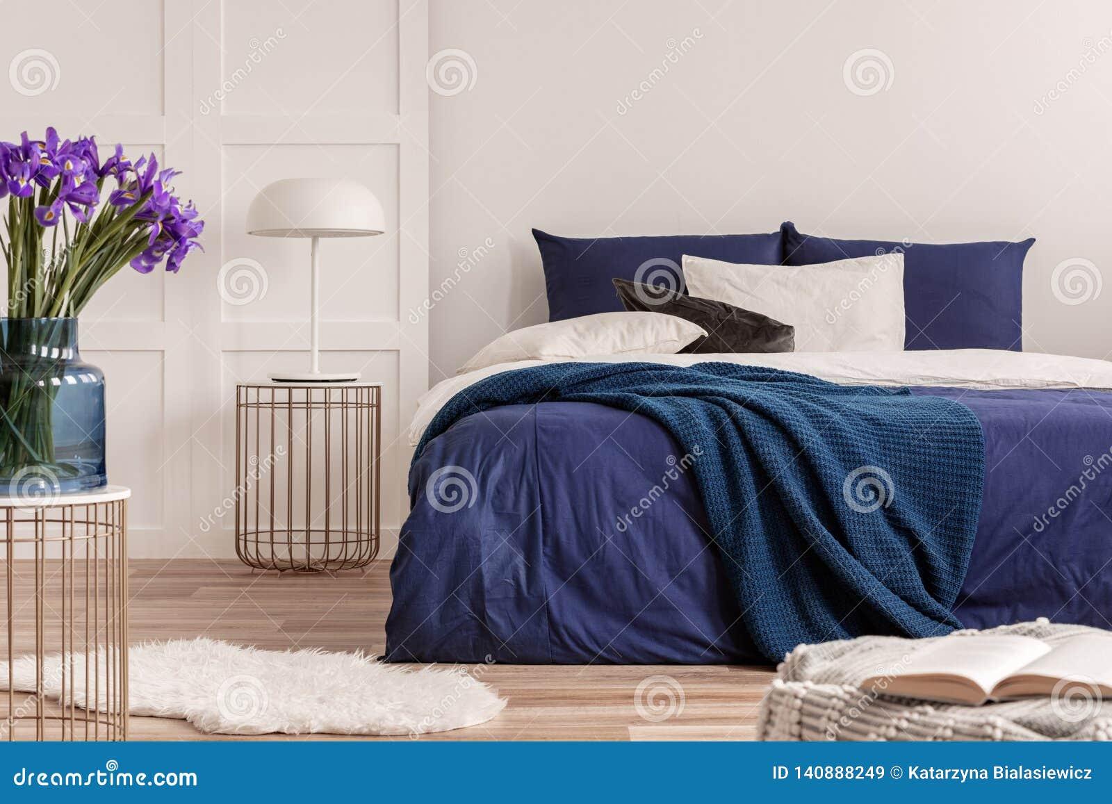 Purpere bloemen in blauwe glasvaas op modieuze lijst in wit slaapkamerbinnenland met comfortabel bed