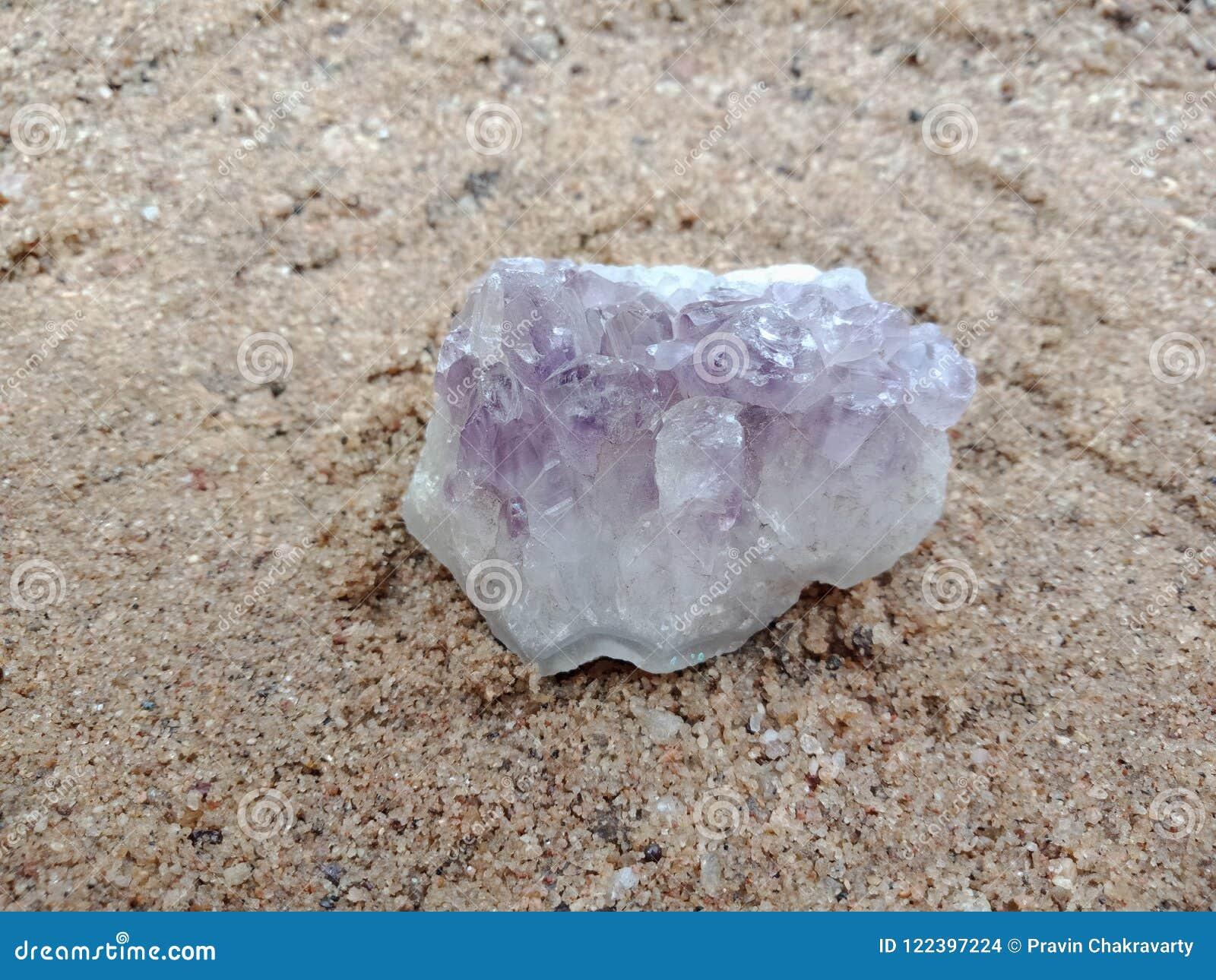 Purpere kristalsteen met textuur op het zand geweven behang als achtergrond, strand Oceaan