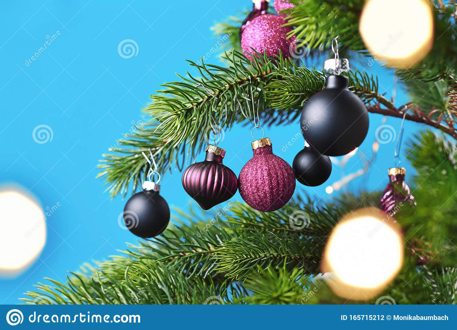 Purple And Black Glass Tree Bauble With Decorated Christmas Tree With Other Seasonal Tree Ornaments On Blue Background Stock Photo Image Of Background Ball 165715212