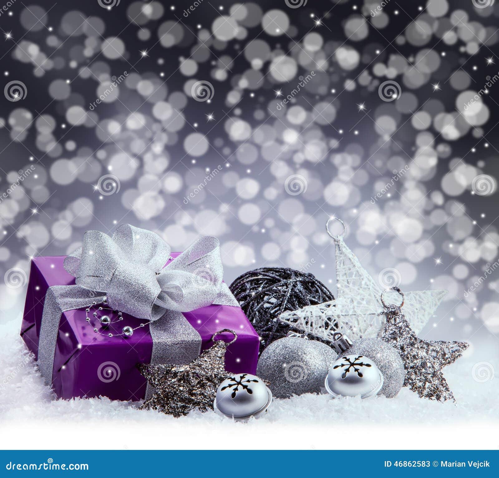 Purple Christmas package , gift of a silver ribbon. Jingle bells , silver christmas balls and christmas stars put on snow.