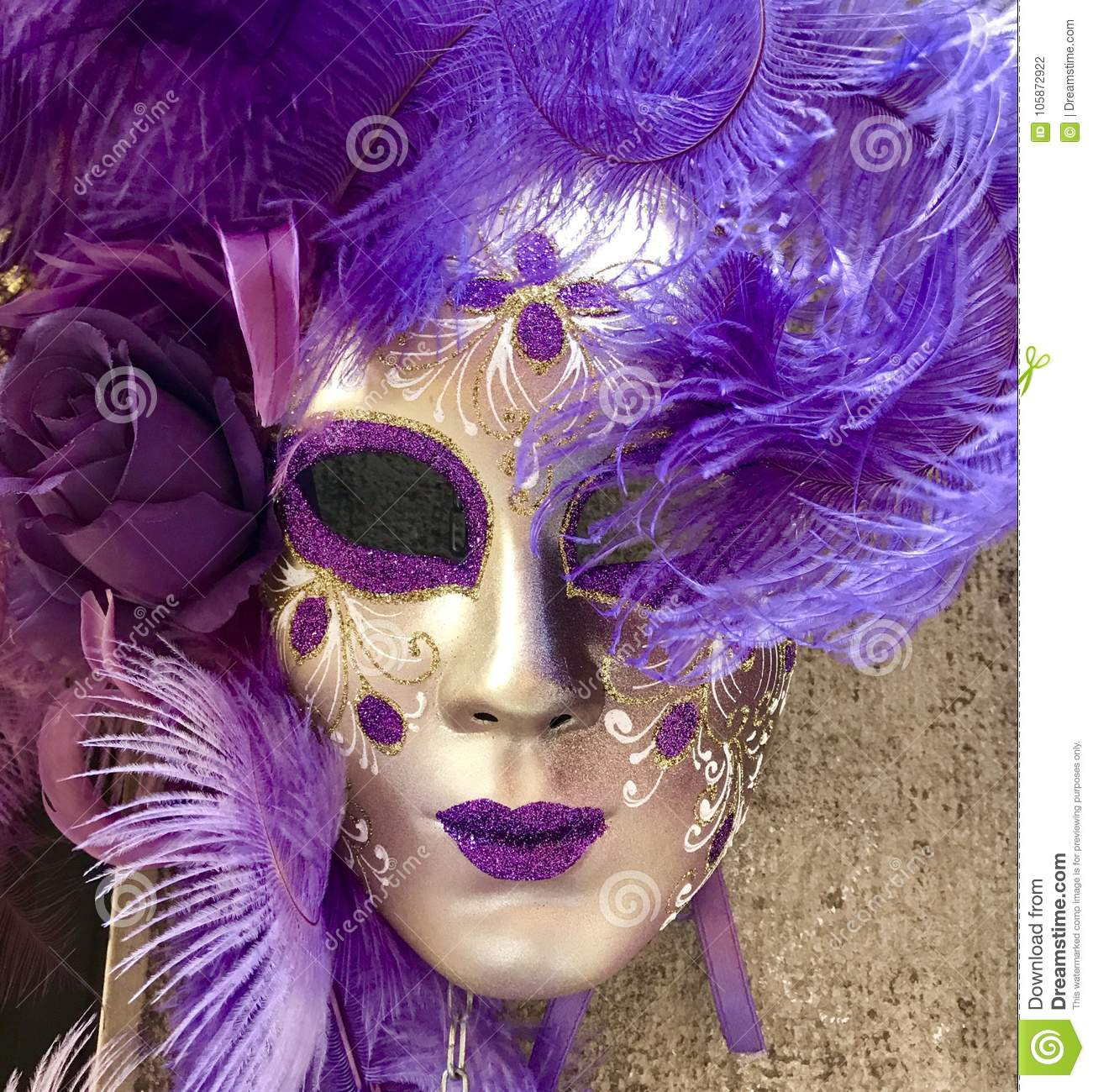 Purple and gold venetian masquerade mask hanging on a wall