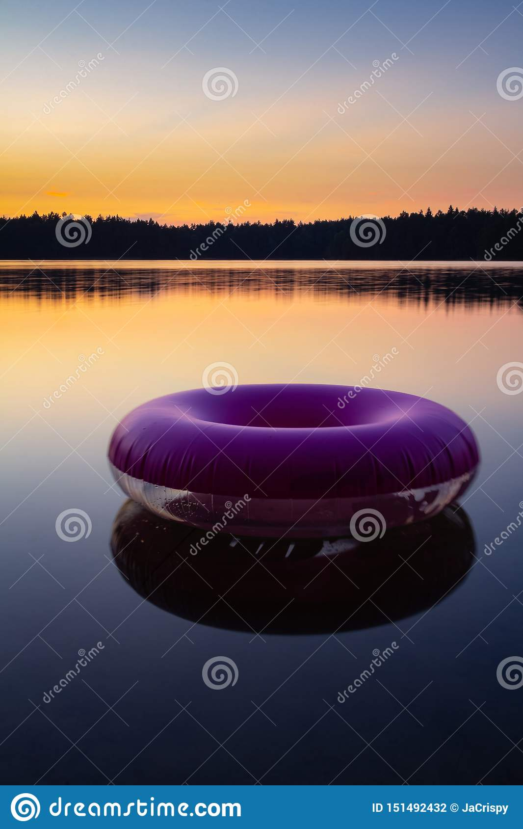 Purple inflatable swimming ring on top of still lake water surface at sunset. Rubber rescue wheel and colourful evening sky and