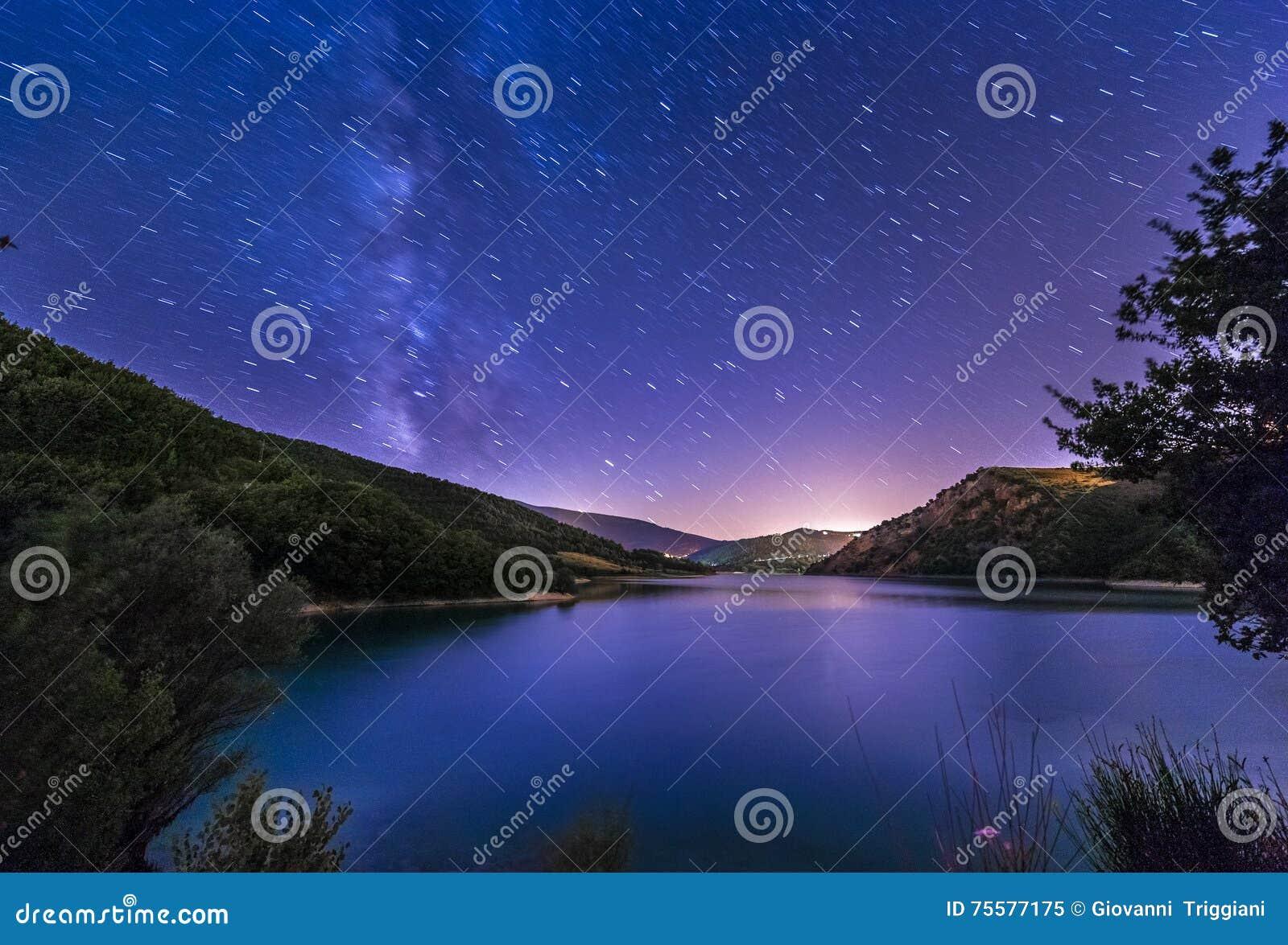 Purple night sky stars lake landscape with milky way on mountain