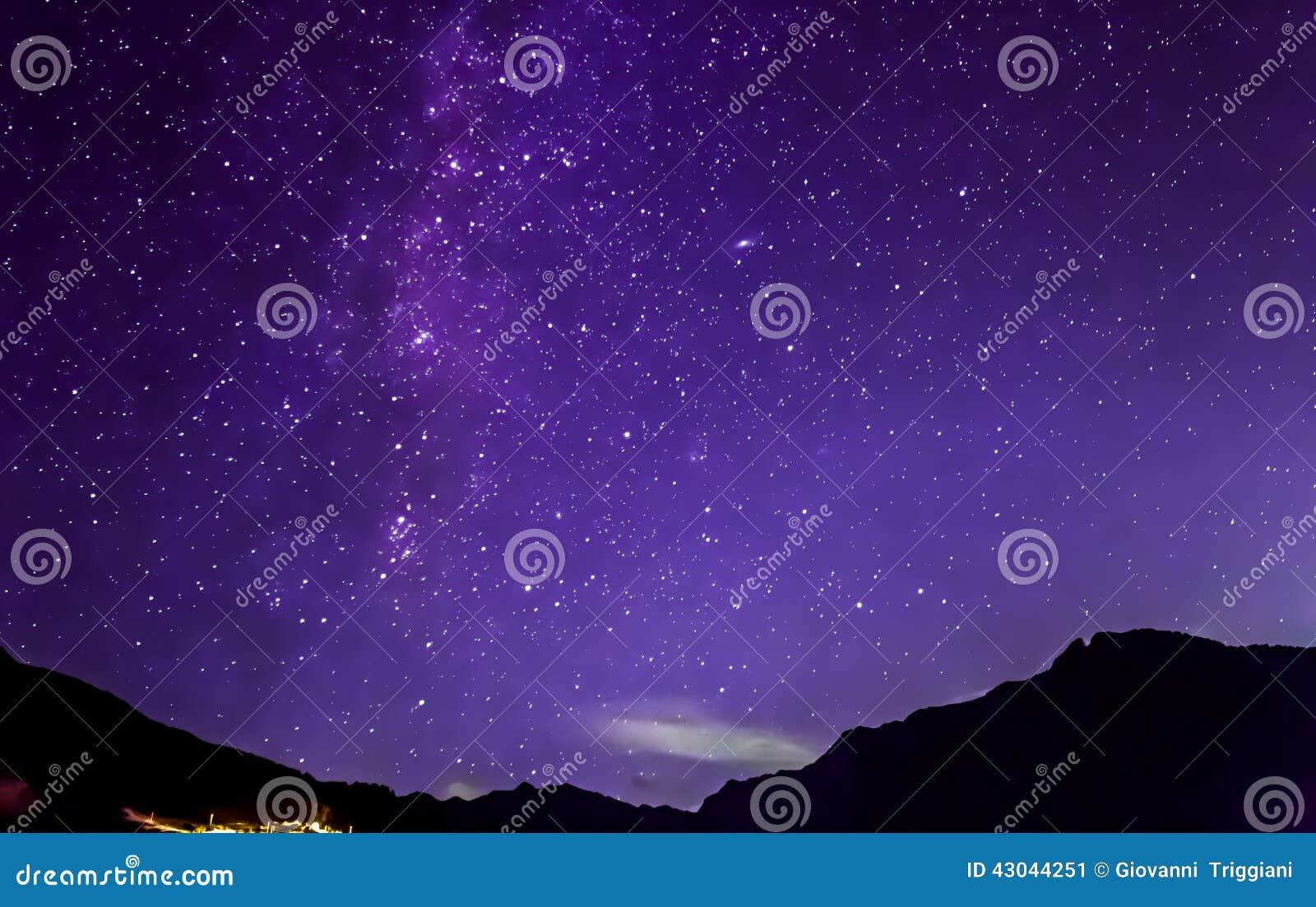 Purple night sky stars. Milky way across mountains