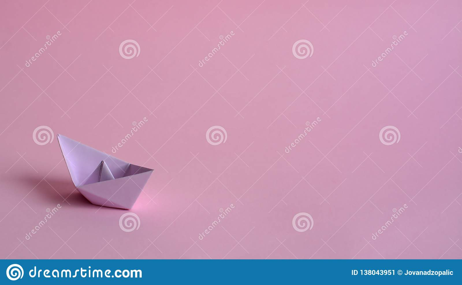 Purple paper boat on a light pink background.