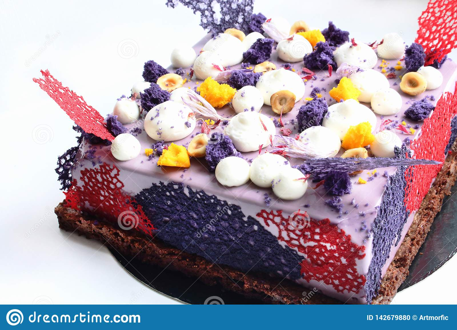 Purple square cake with shiny mirror glaze, cream, nuts and berries