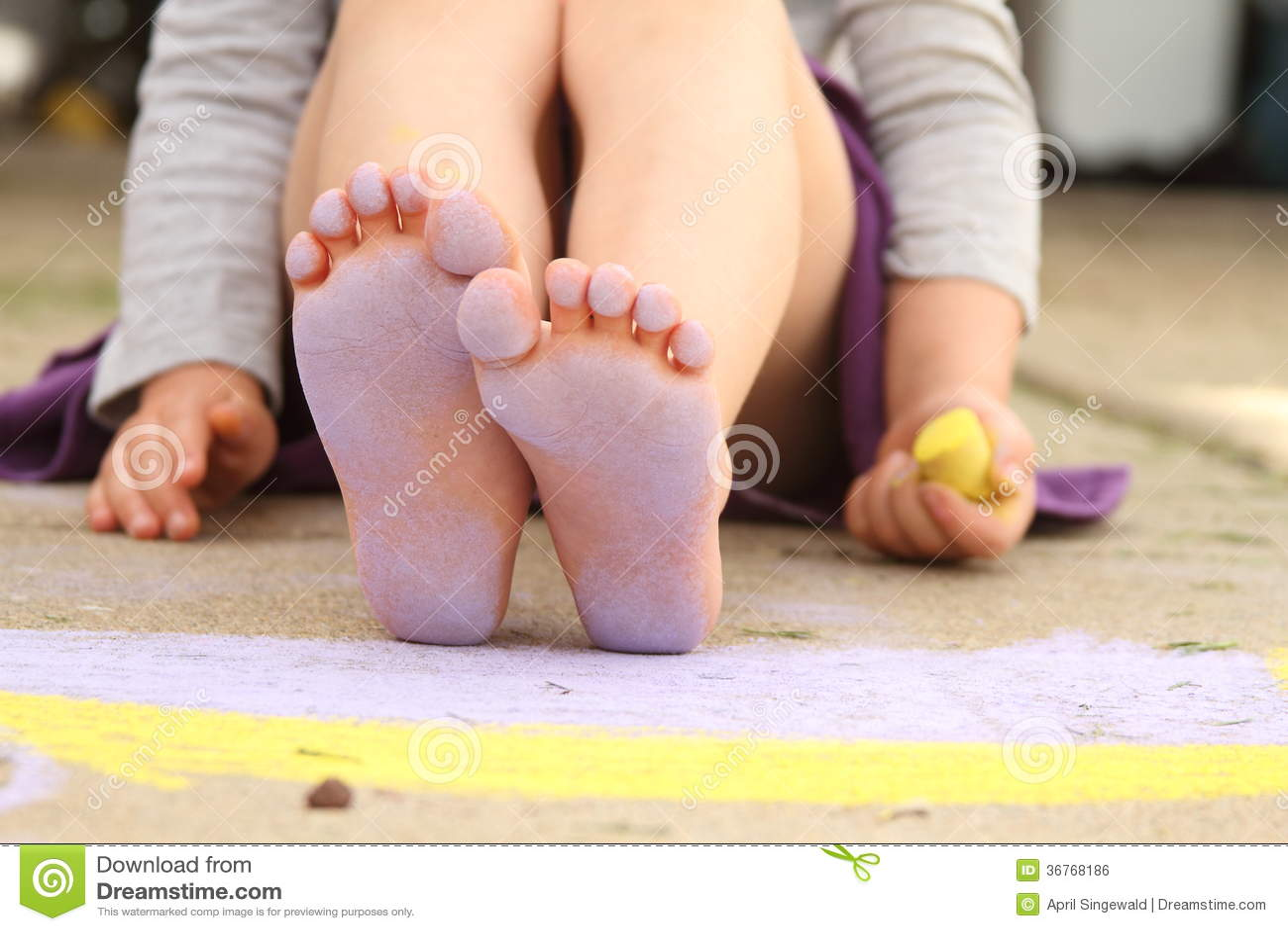 Sidewalk Chalk And A Little Girls Feet Covered In Purple Chalk Dust