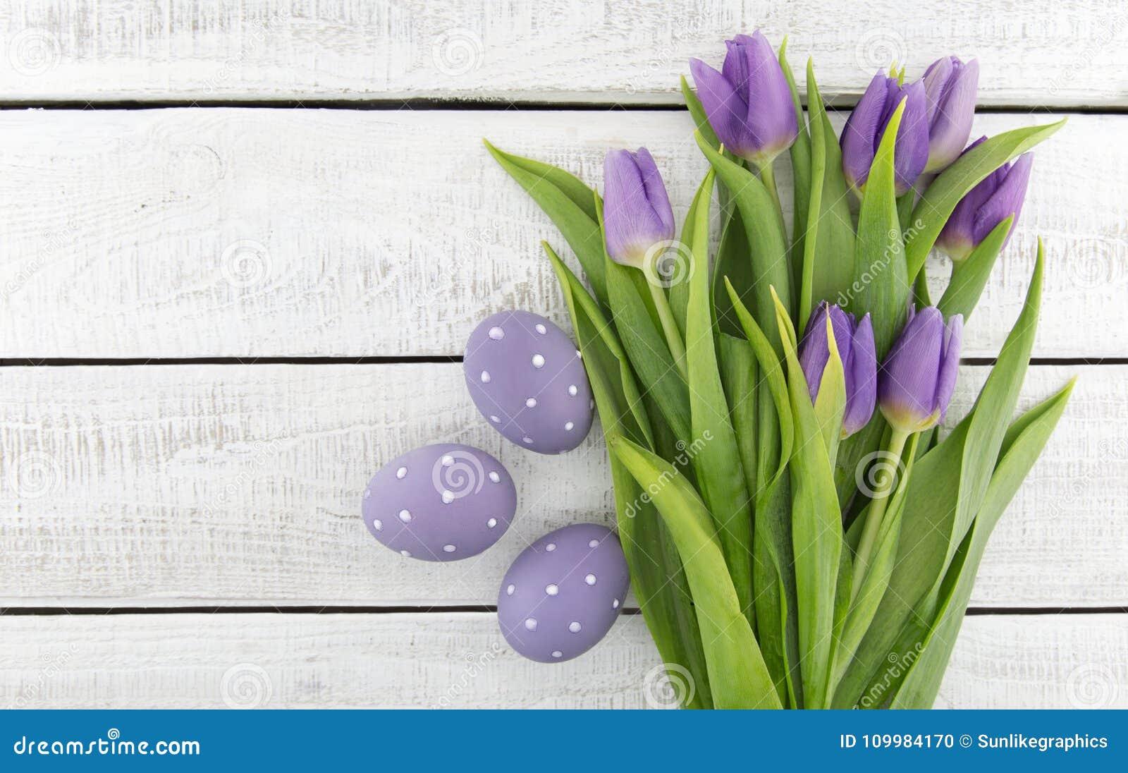 Purpleviolet郁金香和被绘的复活节彩蛋花束在丝毫