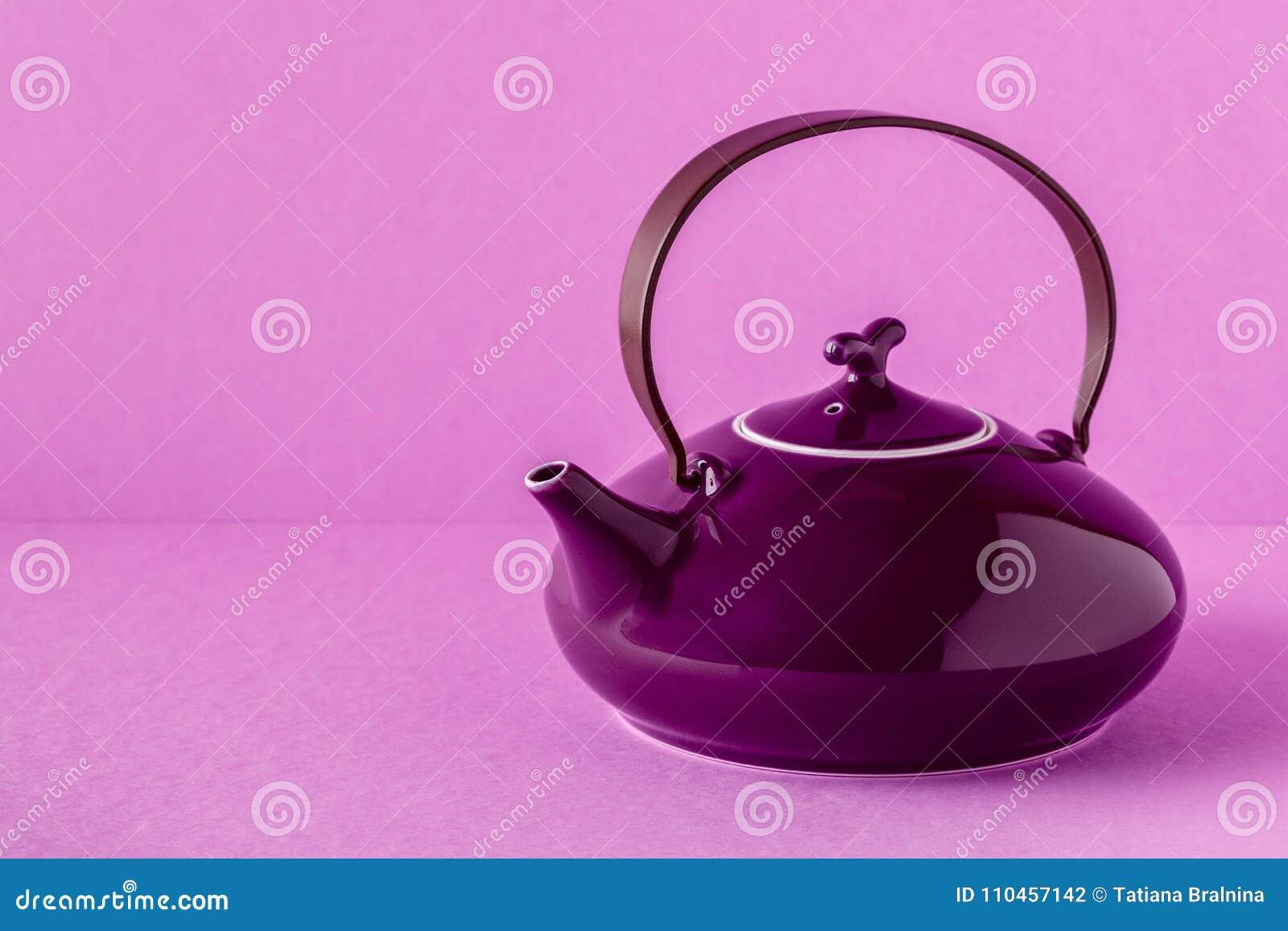 Purpurfärgad tekanna och koppar på en lila bakgrund